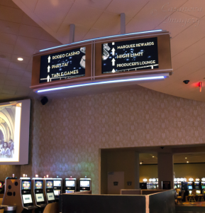 Directional signage from digital content players is displayed on 46in LED TV's mounted in an overhead enclosure.  The content is dynamic, so it can display many different destinations, logos, etc.